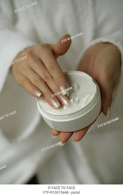 A midsection of a woman holding a box full of white cream