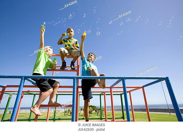 Boys blowing bubbles on monkey bars at playground
