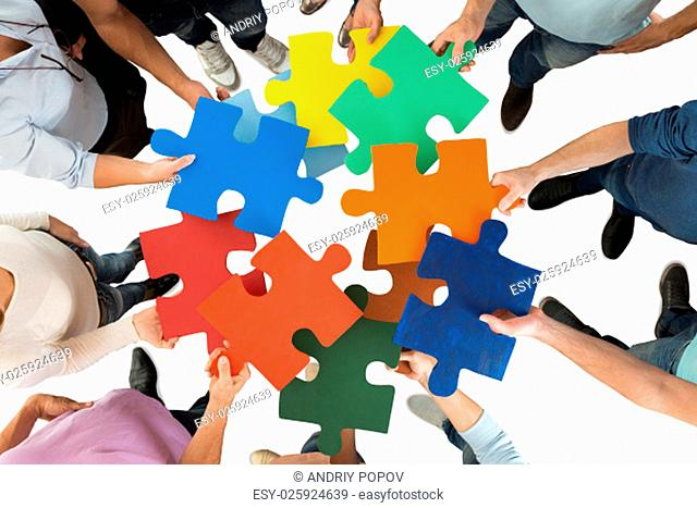 Directly above shot of people holding colorful puzzle pieces in huddle against white background