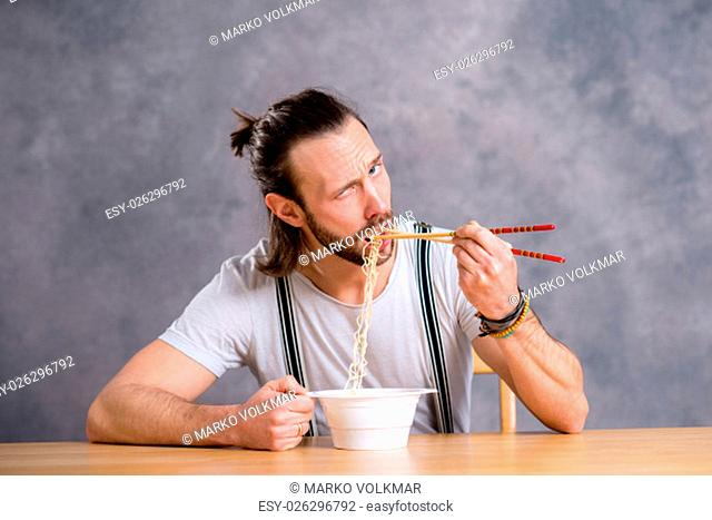 young man eating asian food in front of gray background