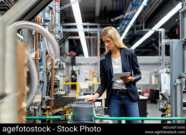 Female manager with digital tablet checking production line in factory