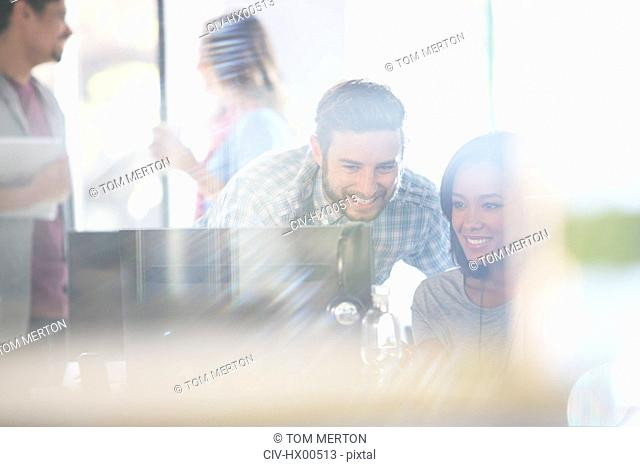Creative business people using computer in office