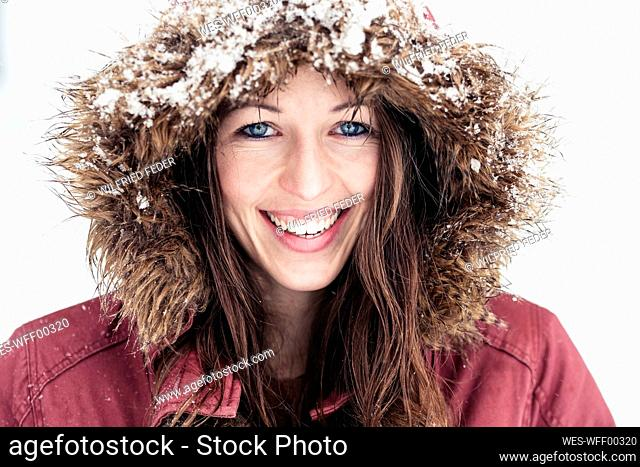 Portrait of laughing young woman with blue eyes in winter
