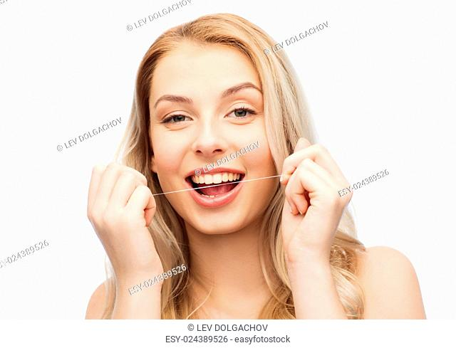 health care, dental hygiene, people and beauty concept - happy young woman or teenage girl with floss cleaning teeth