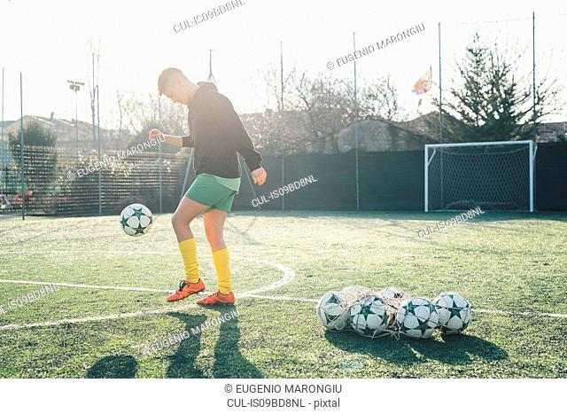 Football player practising on football pitch
