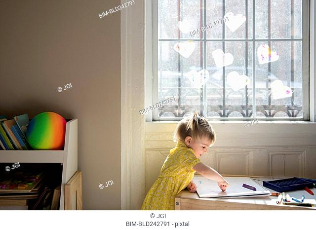 Caucasian baby girl coloring on sketchpad near window