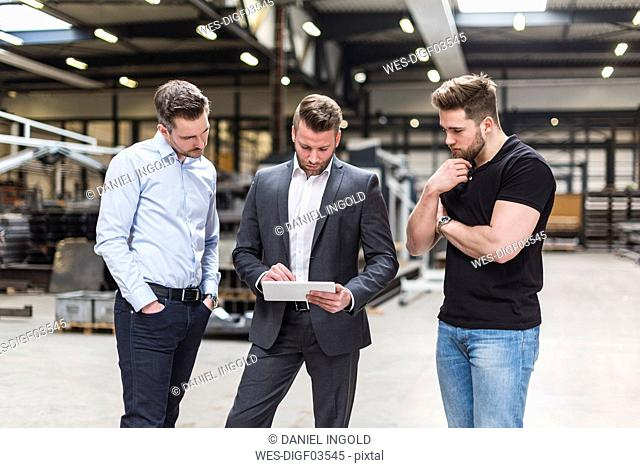 Three men sharing tablet on factory shop floor