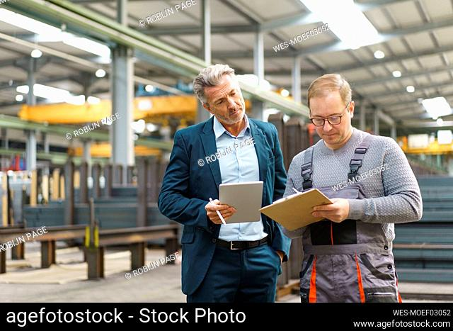 Businessman with tablet and employee with clipboard in a factory