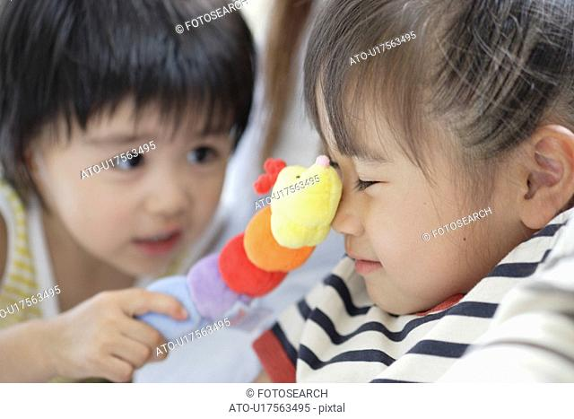 Sister and brother playing with a soft doll