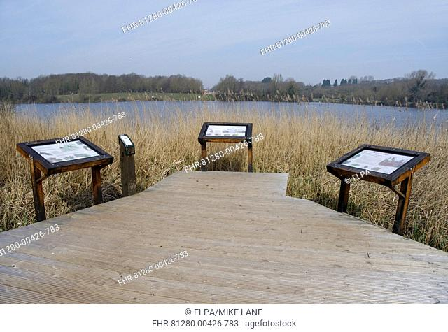 Boardwalk and information boards overlooking lake in flooded former limestone quarry, Cosmeston Lake Country Park, Vale of Glamorgan, Glamorgan, Wales, march