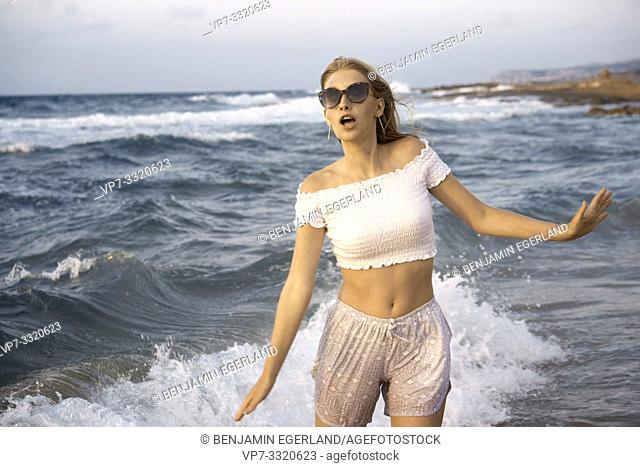 young surprised woman enjoying holiday at beach, open arms, in Crete, Greece