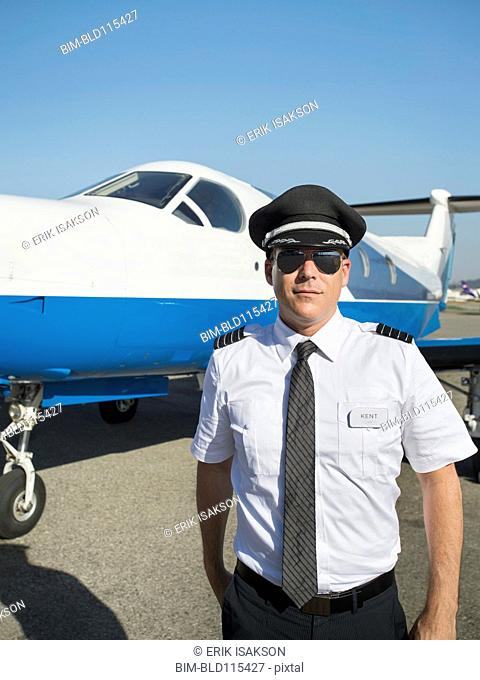 Caucasian pilot by airplane on runway