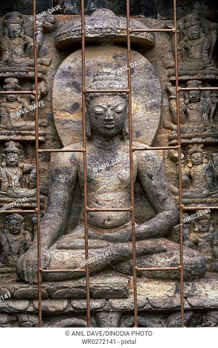 Statue of Buddha behind metal bar in heritage Buddhist excavated site , Udayagiri , Orissa , India