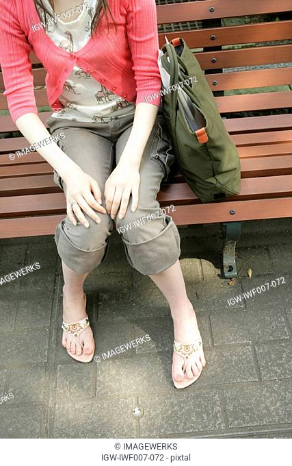 High angle view of hands and legs of a young woman sitting on the bench