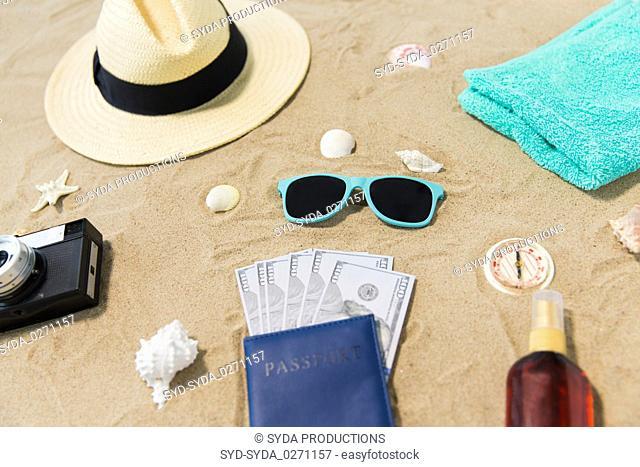 money in passport, shades and hat on beach sand