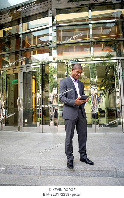 Black businessman using digital tablet outside office building
