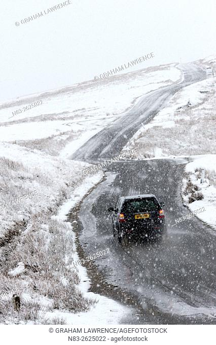 A car negotiates a road through a wintry landscape in the Elan Valley area in Powys, Wales, UK
