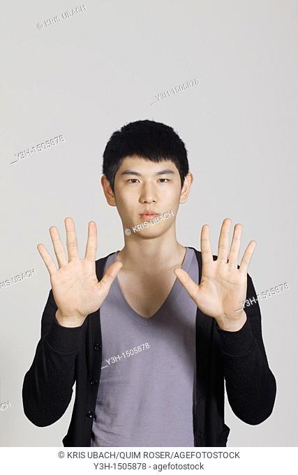 Studio shot of Korean man, showing hands