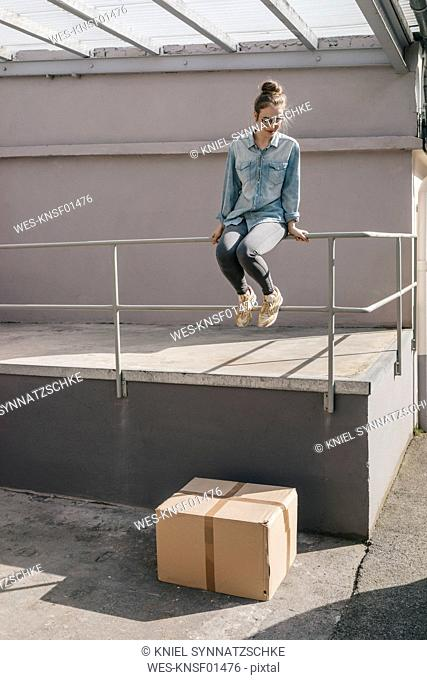 Young woman about to jump on cardboard box