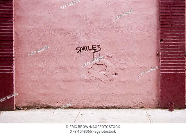 The word 'smiles' is written on a pink wall