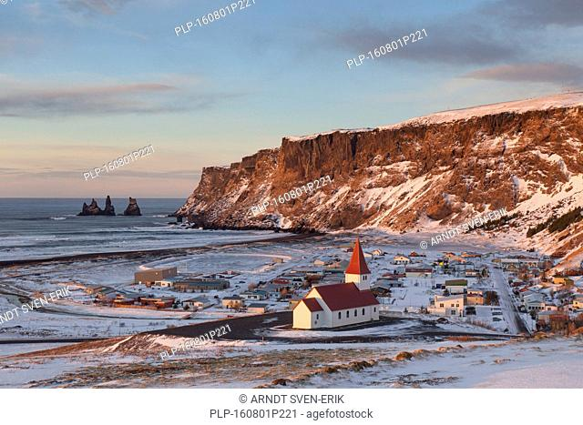 Reynisdrangar sea stacks and the Vík church at the village Vík í Mýrdal in winter, Iceland