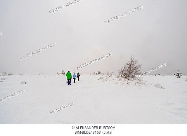 Caucasian women hiking in remote field in winter