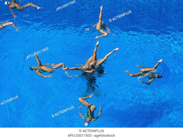 Team of syncronised swimmers upside down in pool