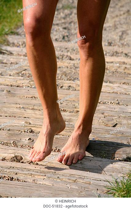 knee shot - legs of a woman walking barefoot on a pathway - trail - multiple-item operation sequence- alley - narrow path - station plank - board