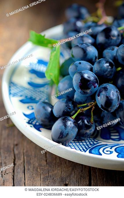 black grapes on plate on wooden table