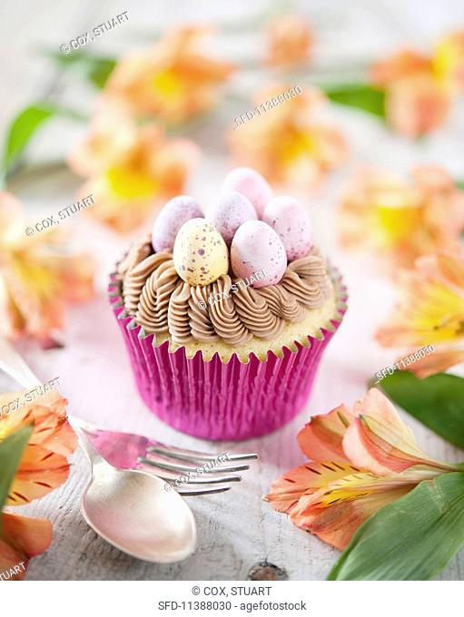 An Easter cupcake decorated with chocolate cream and mini chocolate eggs