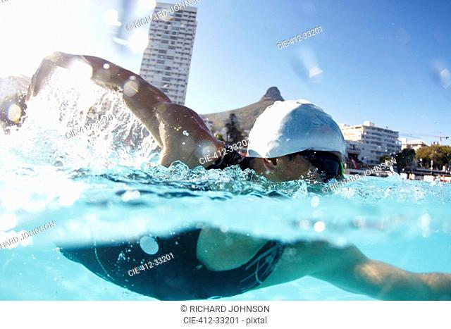 Male swimmer athlete swimming in sunny swimming pool