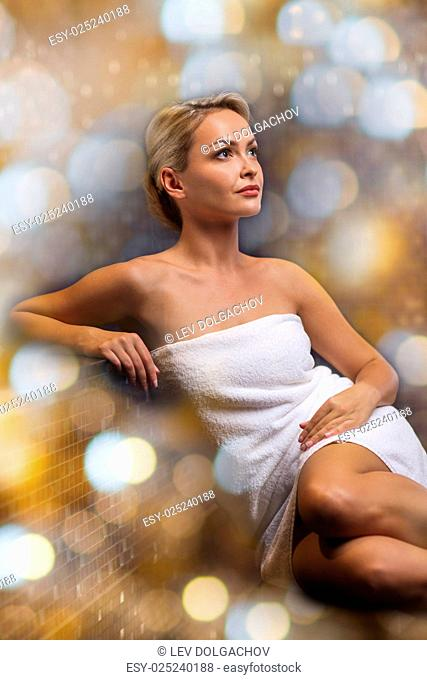 people, beauty, spa and relaxation concept - beautiful young woman sitting in bath towel over holidays lights background