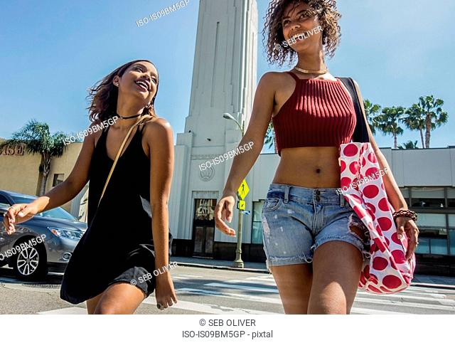 Two young women strolling across pedestrian crossing, Los Angeles, California, USA