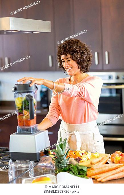 Hispanic woman preparing smoothie in blender
