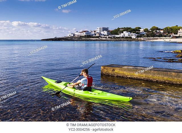 A teenage boy in a Kayak at Punta Prima , Menorca , Balearic Islands , Spain