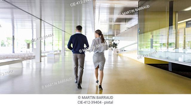 Businessman and businesswoman walking in modern office corridor