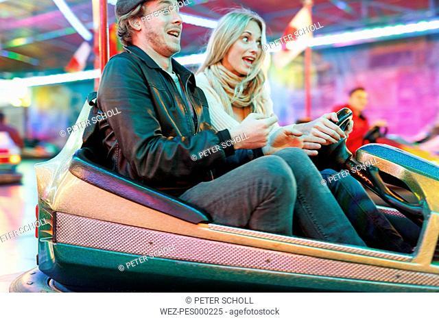 Young couple at fun fair riding bumper car