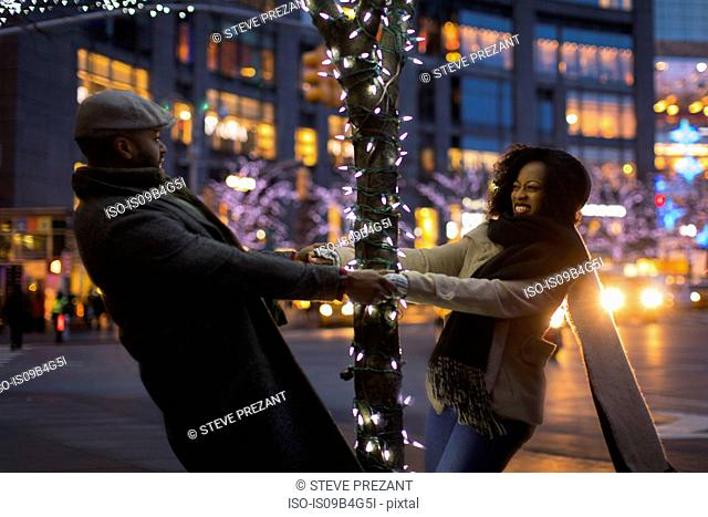 Couple holding hands around illuminated tree at night, New York, USA