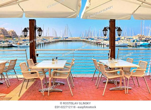 White tables and chairs of outdoor restaurant on promenade along marina on Mediterranean sea in Ashkelon, Israel