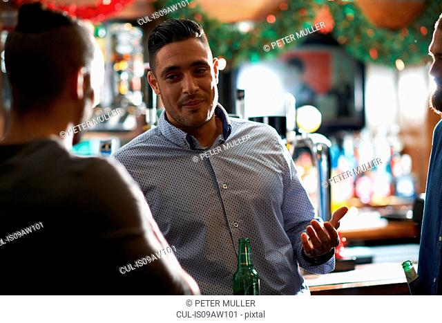 Man leaning against counter in public house talking to friend