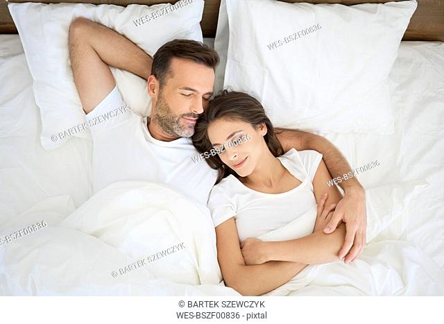 Couple lying in bed, sleeping with arms around