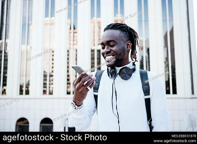 Smiling man with mobile phone against building in city