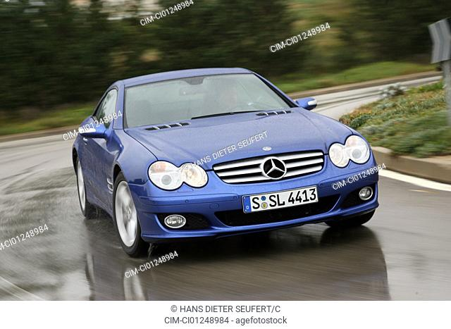 Mercedes SL 500, model year 2005-, blue moving, diagonal from the front, frontal view, country road, closed top