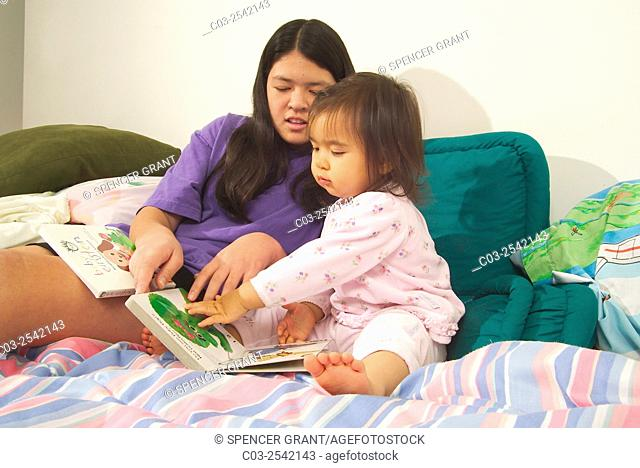 An Asian American teen girl reads to her infant sister in bed while babysitting in Laguna Beach, CA. MODEL RELEASE