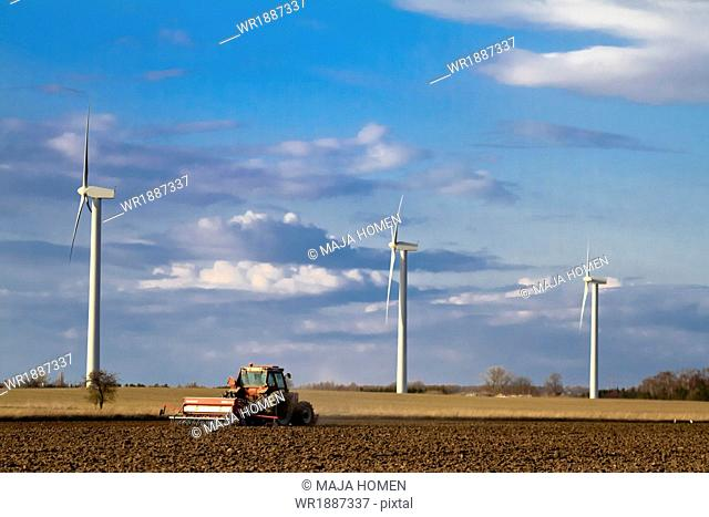 Tractor plowing a field, wind turbines in background, Denmark, Europe