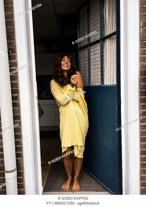 Vucht, Netherlands. Adult, caucasian woman smoking her cigarette while standing on het front door step