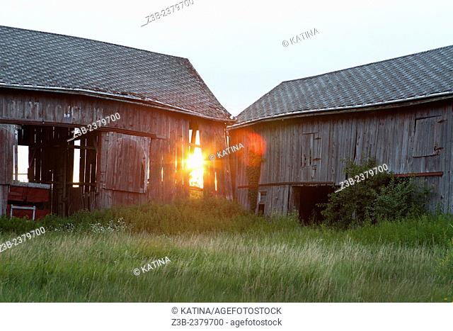 Sunset shines through an old barn in the countryside of Mount Pleasant, Michigan, MI, USA