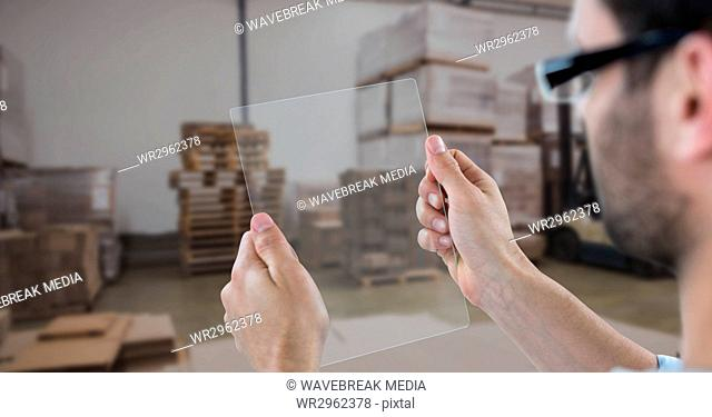 Hands photographing through transparent device in warehouse