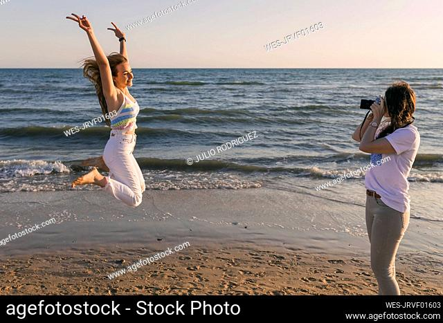 Woman photographing female friend jumping at beach