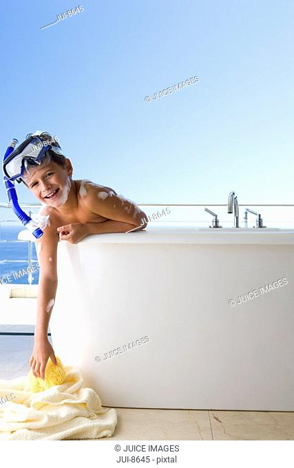 Boy 6-8wearing snorkle in bath outdoors, reaching for towel on ground, smiling, portrait